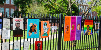 Posters hang on a fence outside Bethesda-Chevy Chase High School at the Black Lives Matter protest on East-West